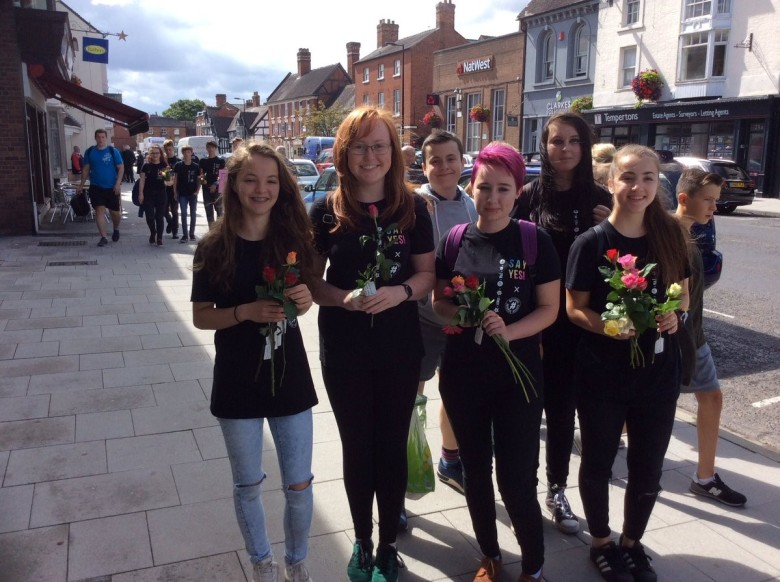 A group of young women giving flowers
